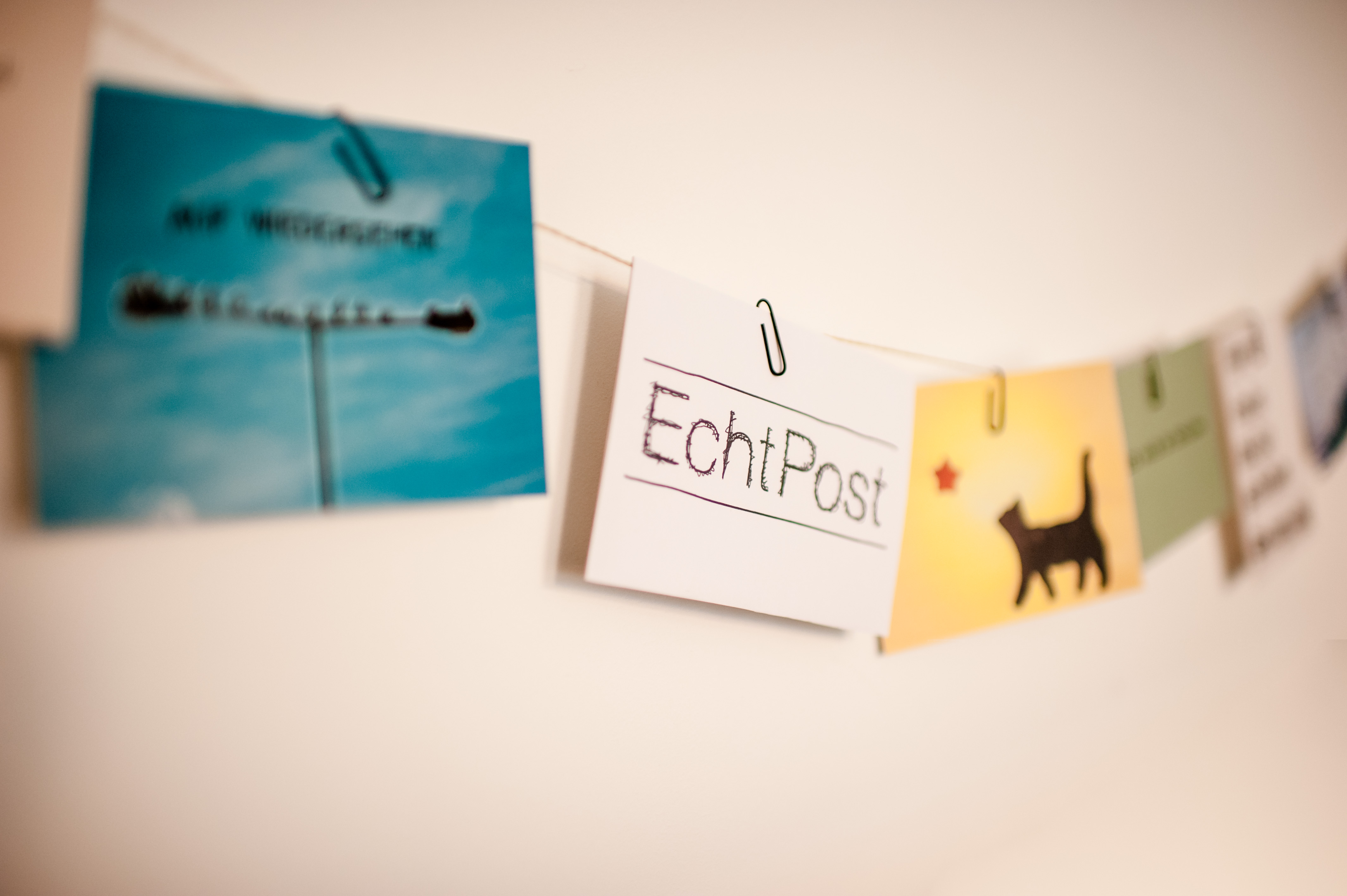 EchtPost-Logo zwischen Postkartenmotiven